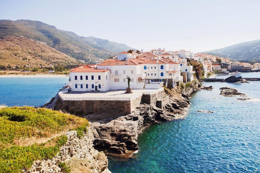 The town of Andros as seen from afar is a stretchy, rocky peninsula with white house and clay brick sloped roofs and a blue sea embracing it all.