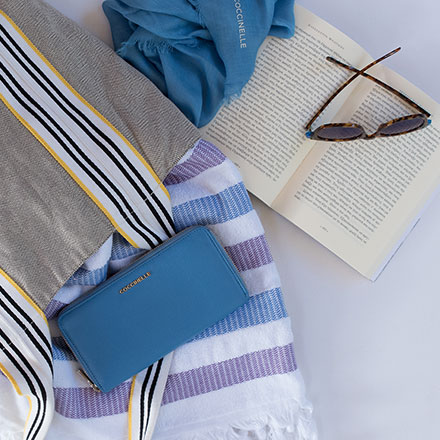 A Coccinelle wallet and peach scarf among a beach towel, sunglasses, open book and fabric beach bag. All casually laid flat. Image by Antonis Drakakis.