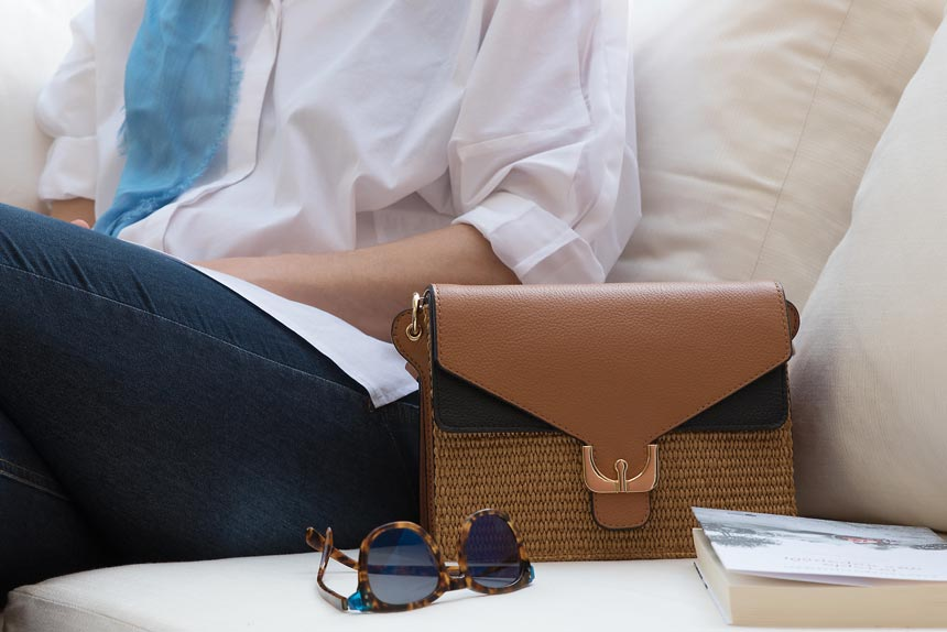 The all-season Ambrine leather and fabric straw bag among a book and sunglasses besides Velvet. Image by Antonis Drakakis.