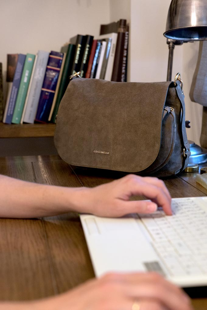 The suede leather Janine bag resting on top of a desk besides Velvet whose typing away on a keyboard. Image by Antonis Drakakis.
