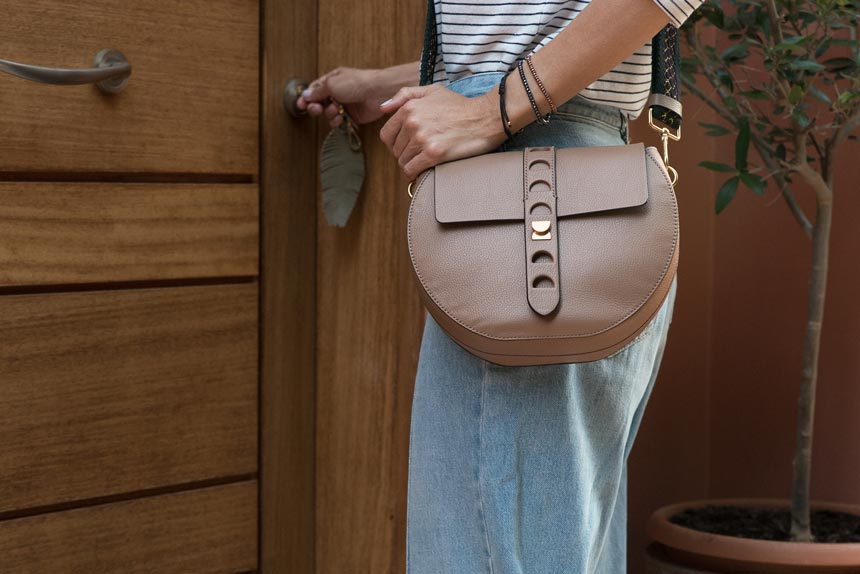 Elisabeth holding the Carousel cross bag in a taupe color and opening her front door with a Coccinelle keyring. Image by Antonis Drakakis.