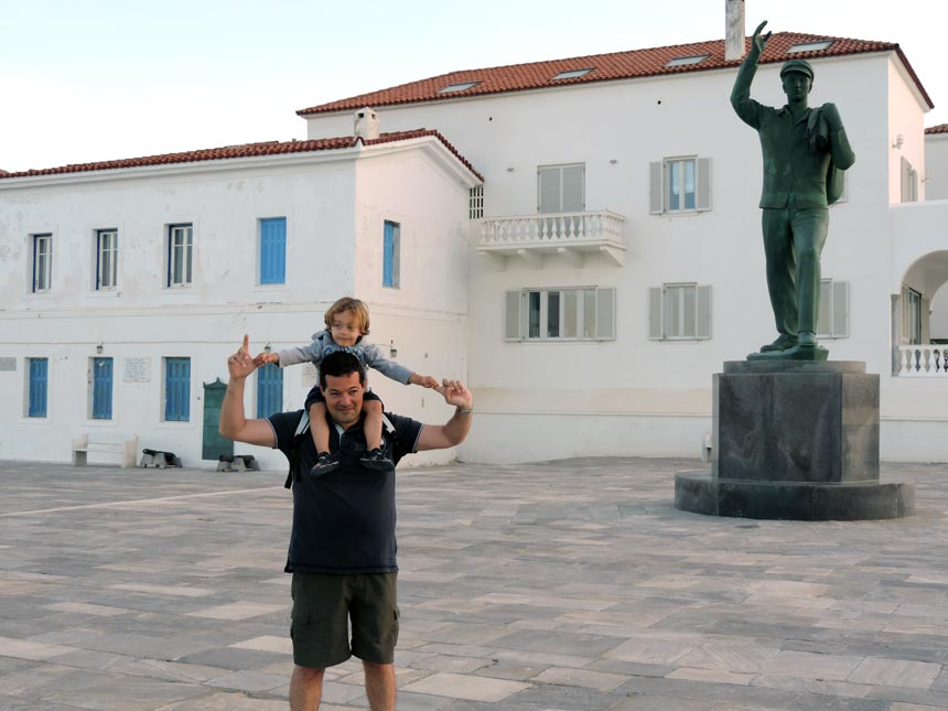 George and my son at the tip of the peninsula. Behind them is the statue in memory to the lost seaman at the town of Andros. Image by Velvet.