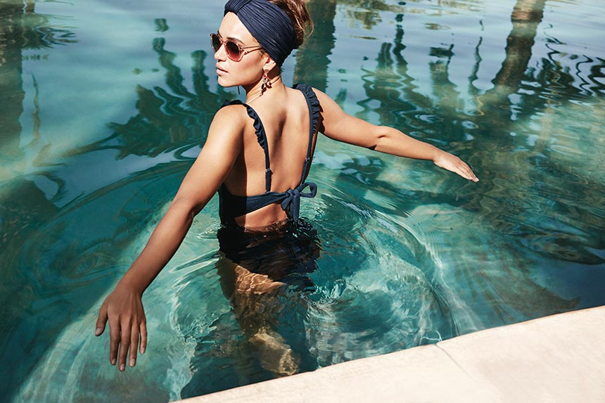 A stylish woman wearing a one piece swimsuit inside a turquoise blue water pool. Image by Accessorize.