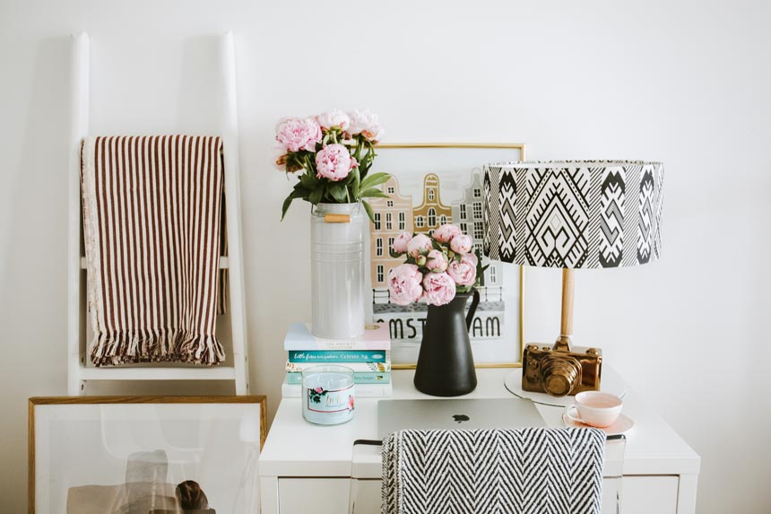 A stylish all white vignette with flowers in vases, patterned textiles that create visual interest along with the table lampshade and art images on the desk.