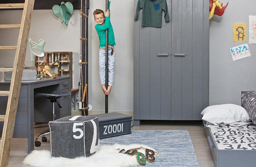 A boy is going down a pole in a bedroom with a Montessori approach. Image by Cuckooland.