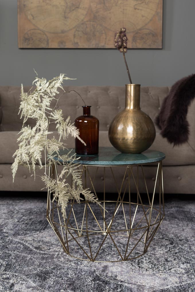 A round coffee table with a green marble top and a brass truss stand with three decorative vases. A brown sofa in the background and a grey area rug on the floor complete the sitting area. Image by Cuckooland.