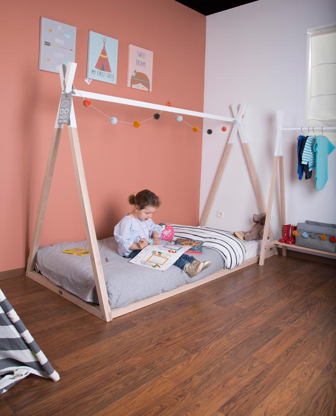 A young child sitting on a floor bed in a Montessori looking bedroom. Image by Cuckooland.