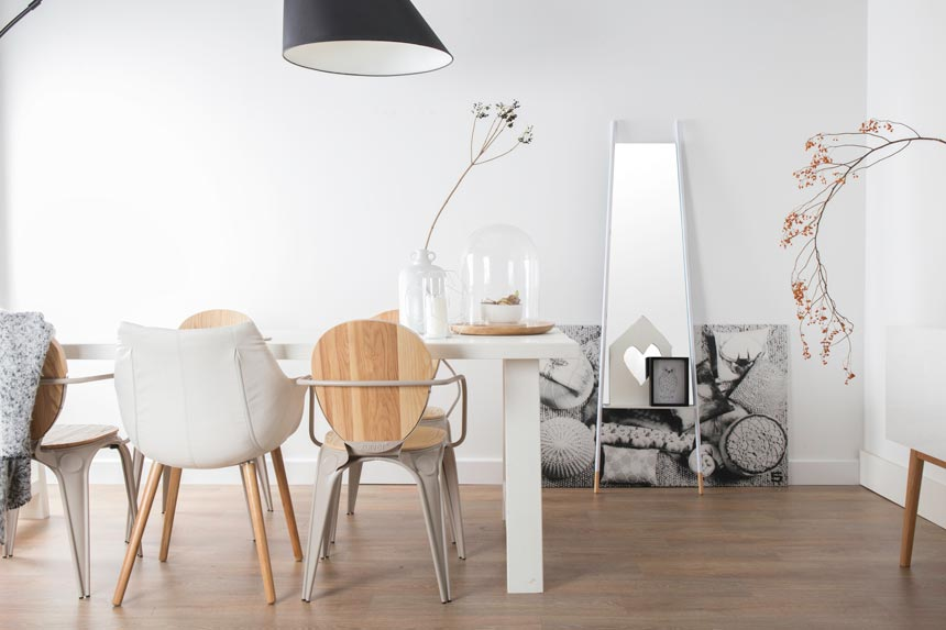 A white minimal contemporary dining room with some warm wooden chairs and a floor mirror in the background that creates an excellent focal point of interest. Image by Cuckooland.