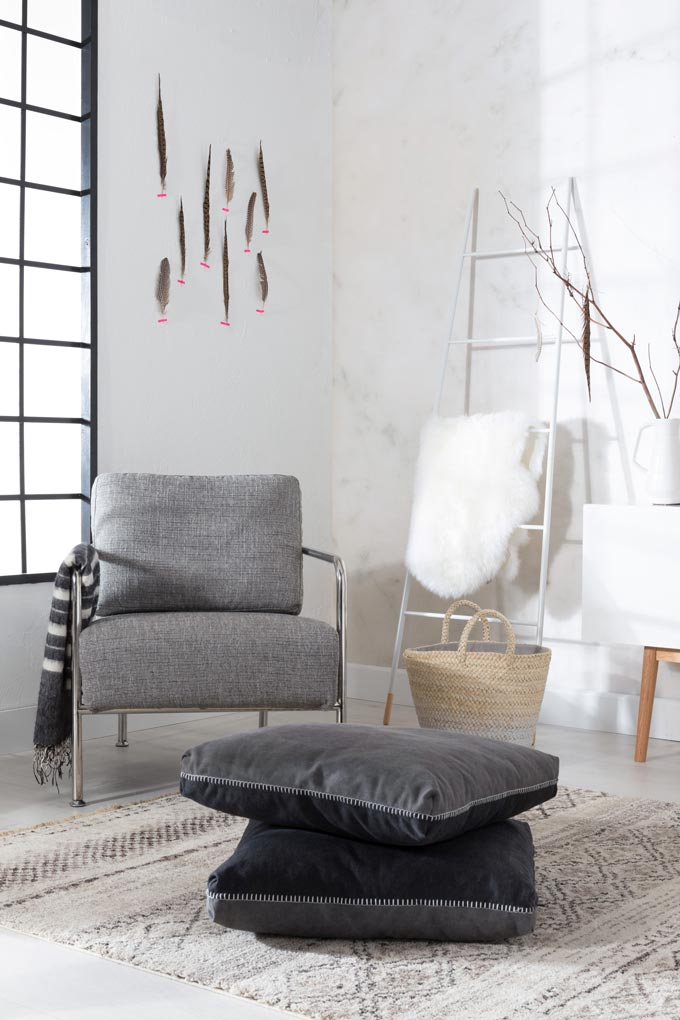 Love the feathers on the white wall in the corner. This minimal vignette with the gray armchair and throw pillows on the floor looks really stylish next to the white decorative ladder and white sideboard. Image by Cuckooland.