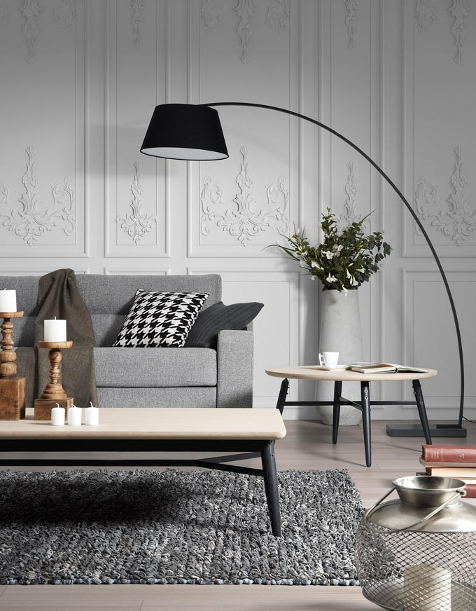 Partial view of a minimal contemporary sitting room. I love the black floor lamp leaning over the gray sofa. The rectangular coffee table is styled with candelsticks at various heights. I also love the contrast between the minimal sofa against the white decorated wall behind it. Image by Cuckooland.
