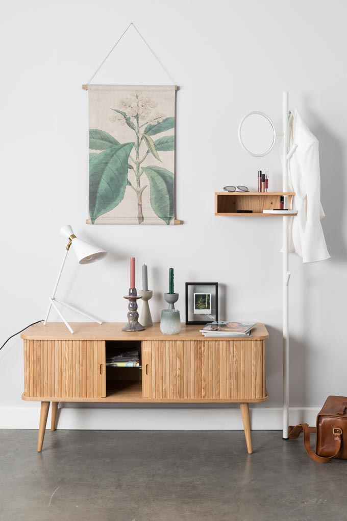A nice contemporary minimal vignette with a lovely sideboard and decor on it. A plant imagery and a wooden shelf on the wall tie it all together, nicely. Image by Cuckooland.