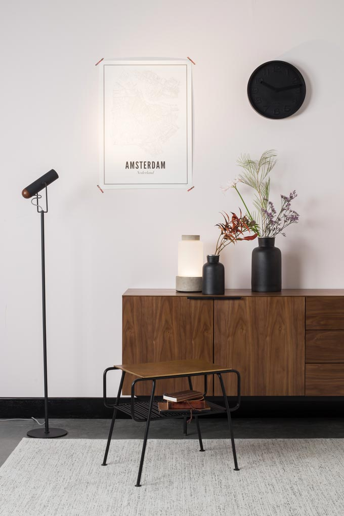 A minimal contemporary vignette with a dark wooden sideboard and decor atop. A map of Amsterdam and a black clock lit by a black slim modern floor lamp create a strong focal point. Image by Cuckooland.