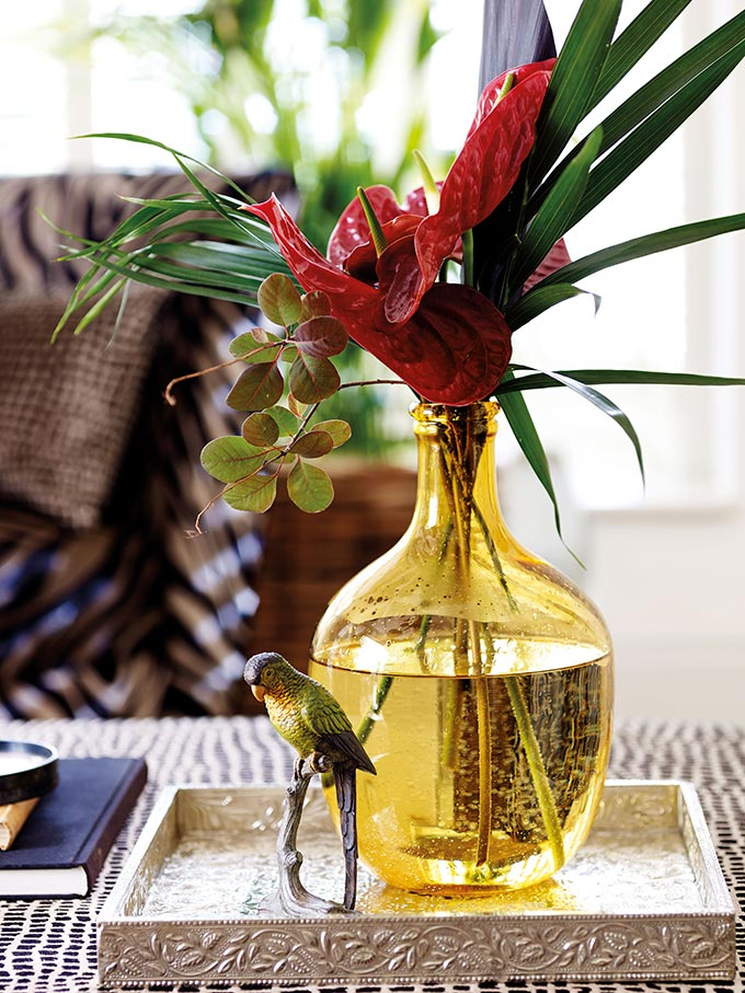 A close detail of a yellow glass vase with a flower arrangement on a tray styled beautifully on a coffee table. Image by DFS Furniture.