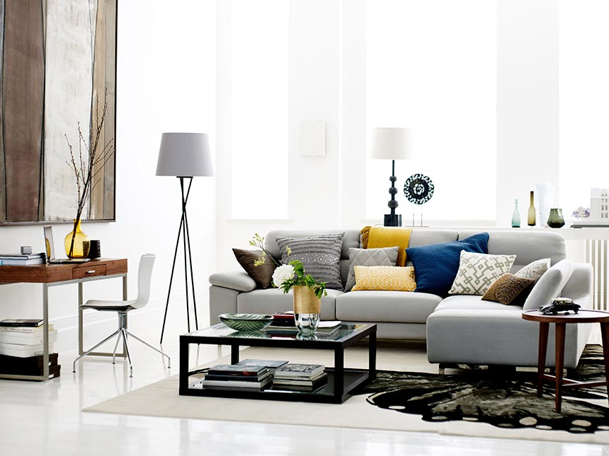 A stylish contemporary living room with that airy grey sectional sofa in the middle and an elegant styled coffee table. Table lamps and floor lamps will create a nice ambiance at night. Image by DFS Furniture.