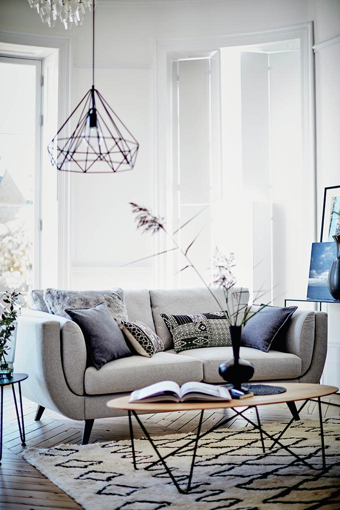 What a lovely grey sofa. I love its curvy shape paired with an oval shaped wooden coffee table in a contemporary minimal sitting room with a Scandi vibe to it. A black pendant light is hanging behind the sofa from this room's high ceiling. Image by DFS Furniture.