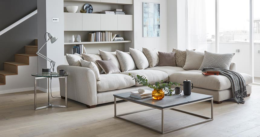 There is a strong sense of serenity in this off white sitting room with a large sectional sofa, a square coffee table in front styled to perfection and a bookcase behind the sofa that plays off beautifully the rest of the setting. Image by DFS Furniture.