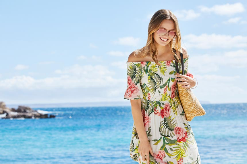A dress with a tropical theme can really have an exotic vibe when worn at a beach resort like this woman does. Image by Dorothy Perkins.