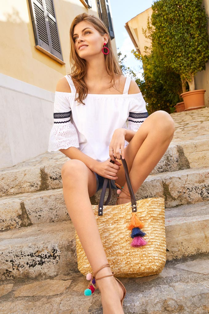 Love this white Bardot top paired with denim shorts and a beach straw bag. A young woman sitting on some outdoor stairs. Imae by Dorothy Perkins.