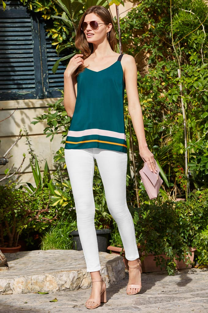 White denims with a dark green cami is such a chic combination. The model is also holding a pink clutch bag - nice touch. Image by Dorothy Perkins.