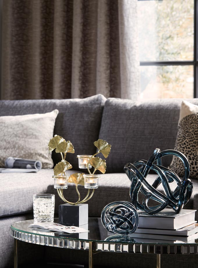 Love the two metallic and glass sculptures sitting atop a stack of books on a styled coffee table. Image by Dunelm.