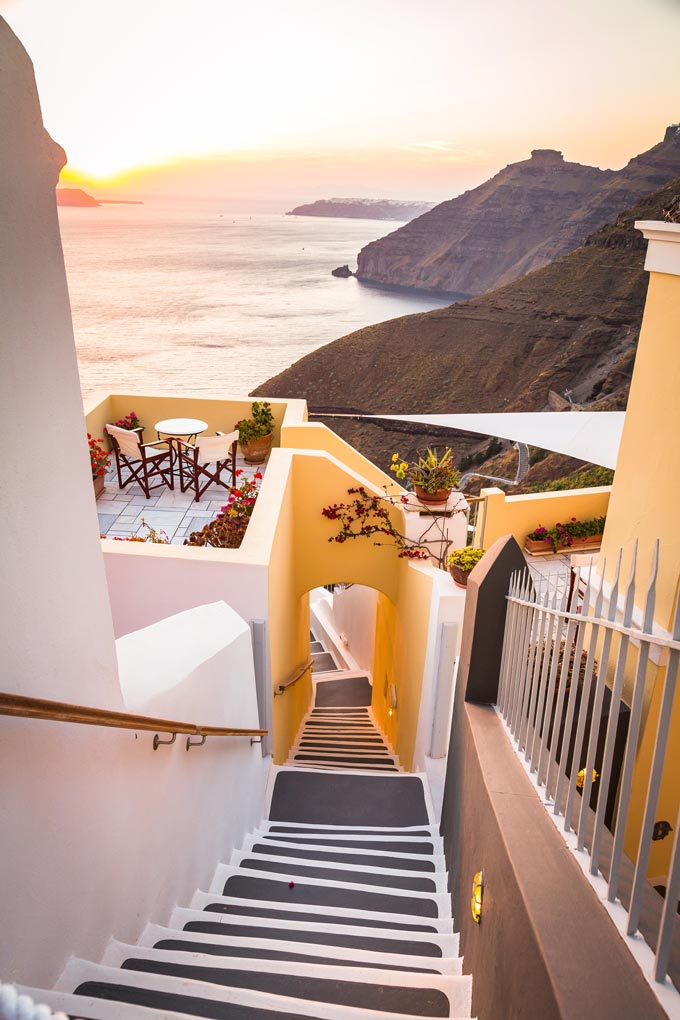 A staircase between homes in Fira Santorini with a breathtaking view of the Aegean Sea.