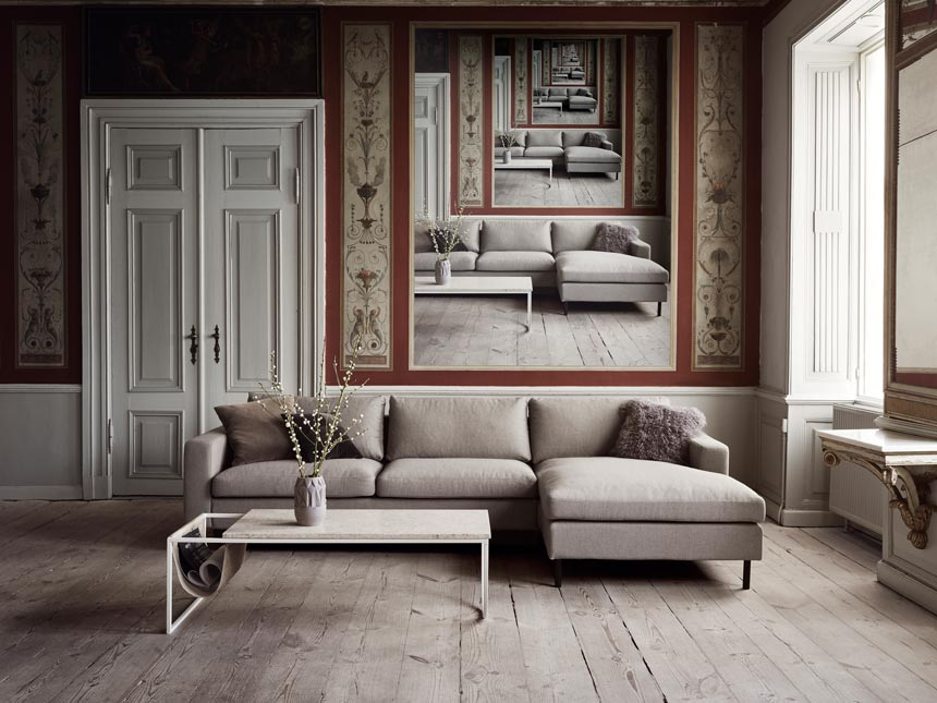 I love this gray minimal sectional sofa with a white marble coffee table in a high ceiling room with wall murals and a white decorative double door. Image by Houseology.