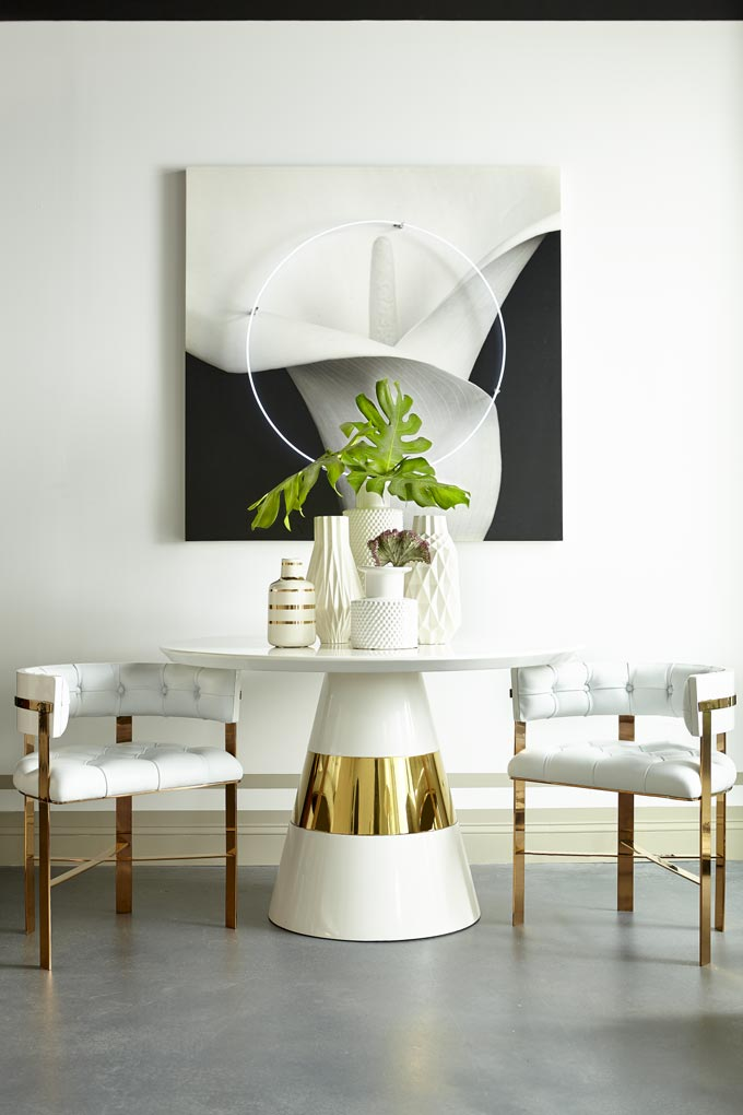 An all white contemporary dining vignette with a round table and chairs with brassy legs, a large black and white art image on the wall. Image by Houseology.