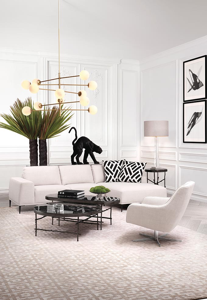 What a stylish minimal, eclectic sitting room, all in white but lots of inky stains like the art images on the walls, the two black coffee tables, the large black vase that holds the green foliage and top all that with a chic brassy chandelier. Image by Houseology.