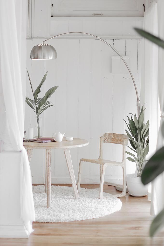 A round whitewashed table and chair with plants and a chrome floor lamp besides it in a deliciously white room.