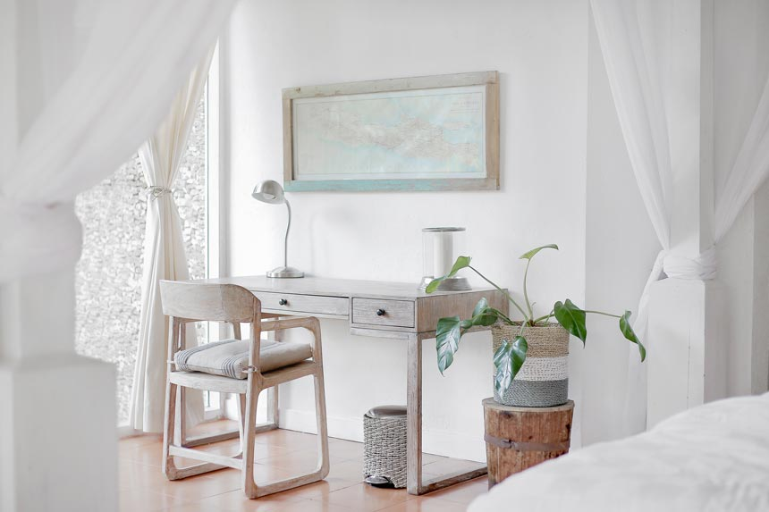 A weathered looking whitewashed desk and chair in an all white room looks as the perfect match. A plant and a whitewashed framed map over the desk ties it all together really nicely.