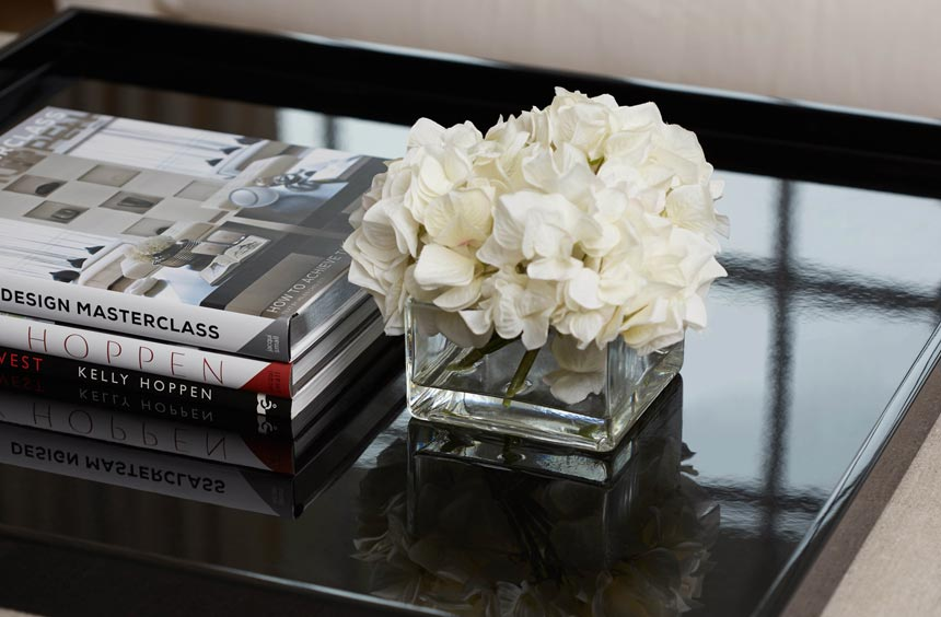 Close up of a black coffee table with a cube glass vase and white flowers in it and a stack of three books besides it. Image by Kelly Hoppen.