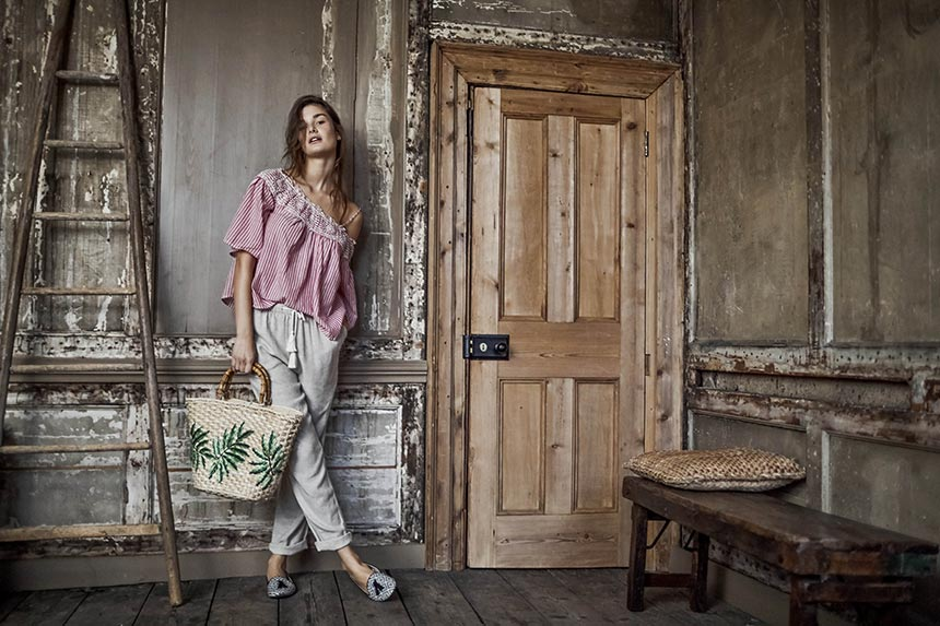 Love the worn out house interior as a background to a woman dressed so casually with a striped red top, light grey sweat pants, sliders and a straw bag. Image by Matalan.