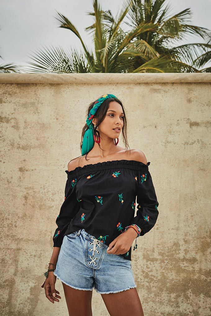 How can you not love a black Bardot top combined with denim shorts and a green headband in the hair like this model. Image by Matalan.