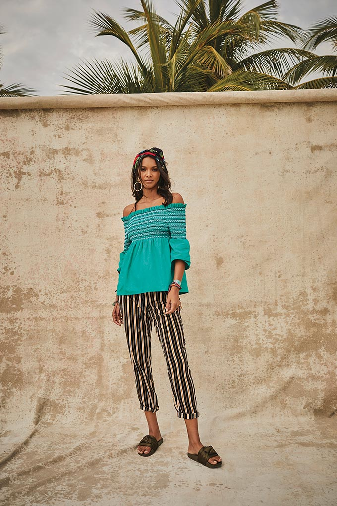 A lovely bright combination of a turquoise green Bardot top paired with back and gold yellow striped pants. They are paired nicely with some khaki sliders and it all looks great on this brunette model. Image by Matalan.