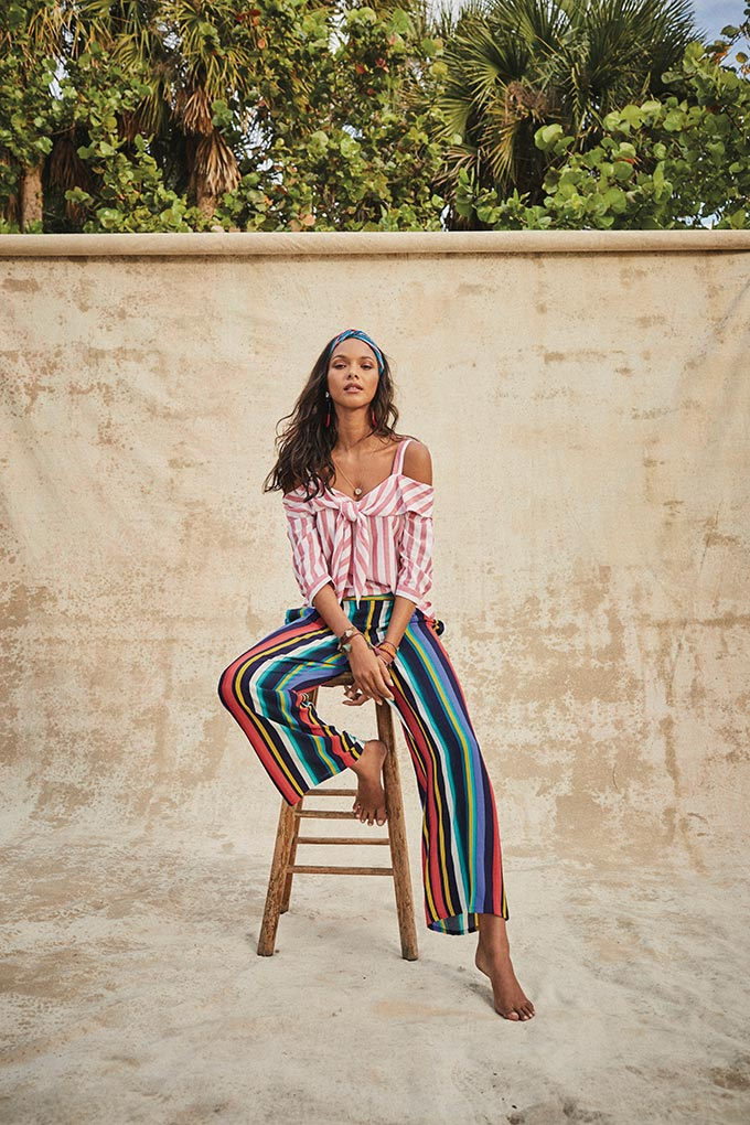 Statement stripes. A woman sitting on a stool shows off her pink and white stripe Bardot top paired with wide leg pants with rainbow stripes. Image by Matalan.