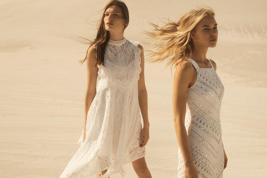 Love both white summer dresses. They are worn by two beautiful women on a windy day with sandy dunes in the background. Image by Monsoon/Accessorize.