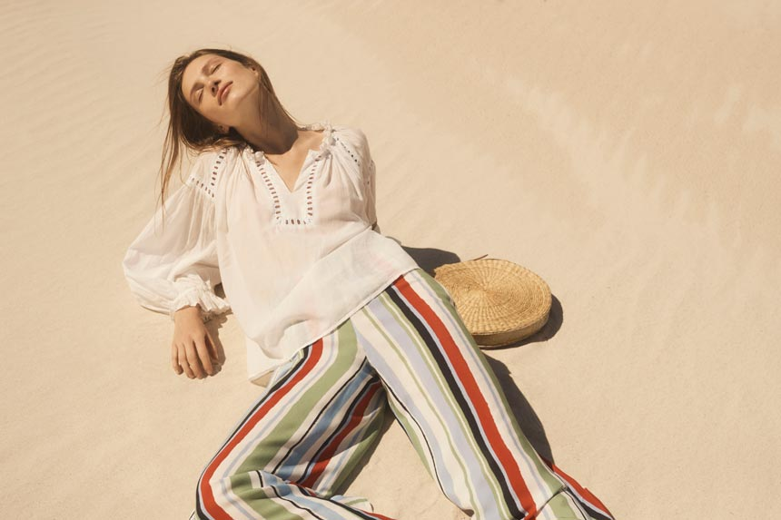 Love this combo of a white boho style shirt and striped wide leg pants paired with a round straw bag as seen by this model who's laying on the sand. Image by Monsoon/Accessorize.