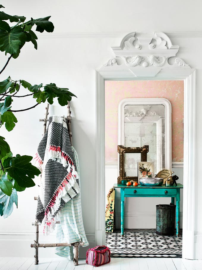 View of a turquoise boudoir against a blush pink wall, through a series of door openings. Textiles hanging by a white ladder by the door add even more texture and a boho flair. Image by Monsoon.