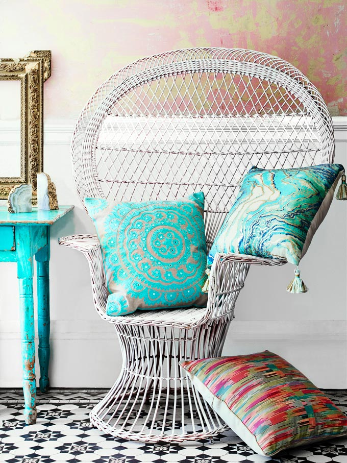 An armchair besides a turquoise boudoir is styled with patterned throw pillows to add that carefree boho flair to it all. Image by Monsoon.