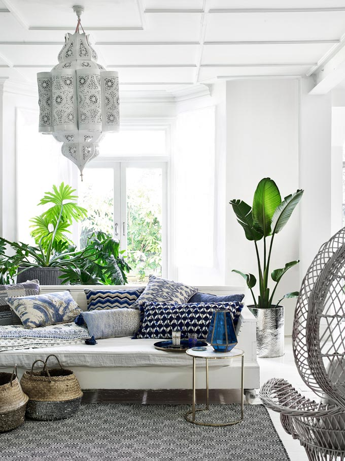 A bohemian styled white sitting room with a large Moroccan hanging latern, plants and seagrass baskets as decor. Image by Monsoon.