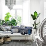 A white sitting room with a bohemian flair to it because of the white hanging Moroccan lantern, the seagrass baskets in front of the white sofa, the blue patterned throw pillows, the plants and the peackock fan white armchair. Image by Monsoon.