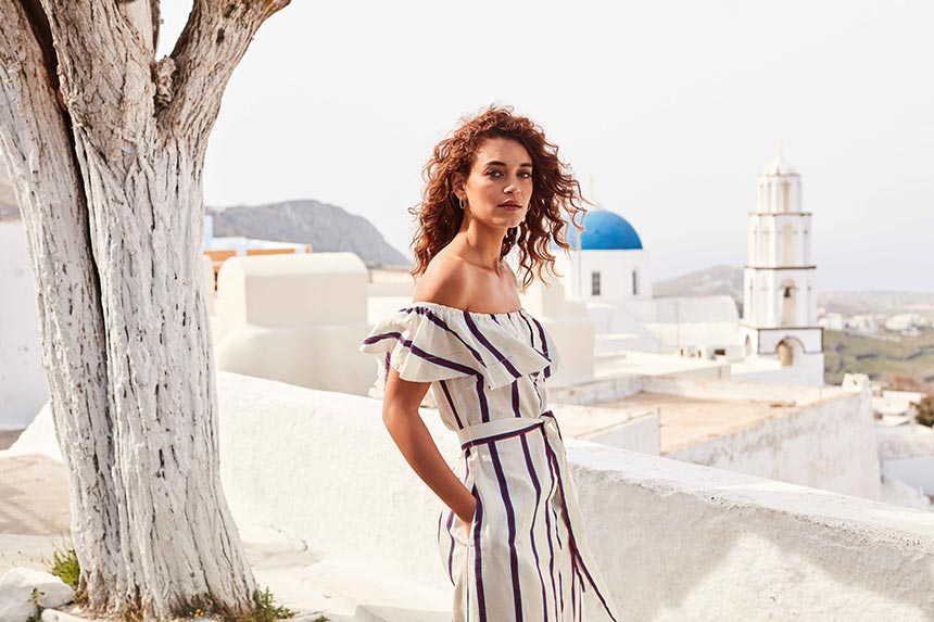 A Bardot style white dress with stripes is both stylish and feminine - ideal for wearing in Santorini, just like this model. Image by Monsoon/Accessorize.