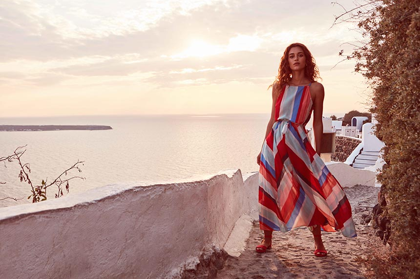 How chic! A beautiful woman wearing a long summer dress with red and blue stripes and has the sunset of Oia in Santorini as her backdrop. Image by Monsoon/Accessorize.