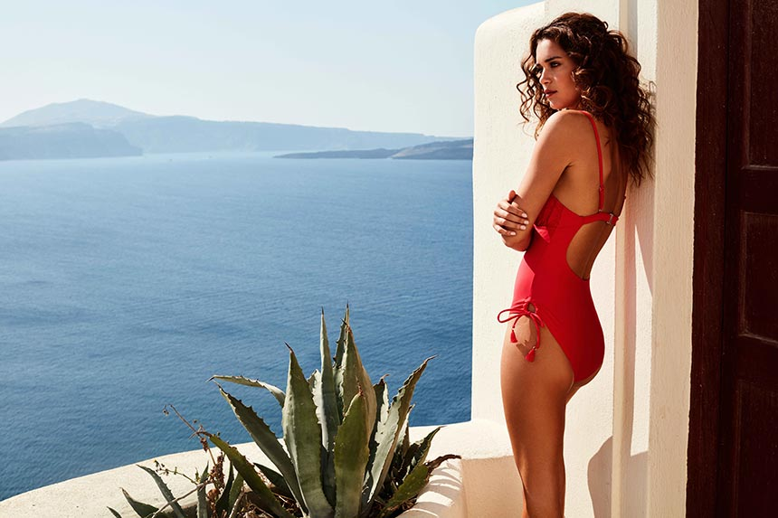I love a red one piece swimsuit just like this worn by a model who's gazing at the incredible sea view from Oia Santorini. Image by Monsoon/Accessorize.