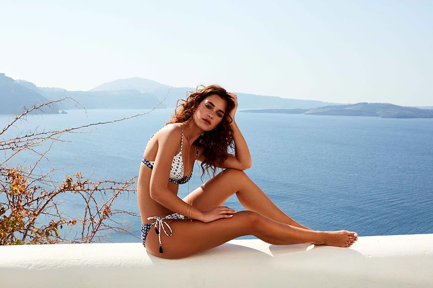A beautiful bikini worn by a model who's resting on a short wall somewhere in Oia, Santorini with the Aegean Sea in the background as the perfect backdrop. Image by Monsoon/Accessorize.
