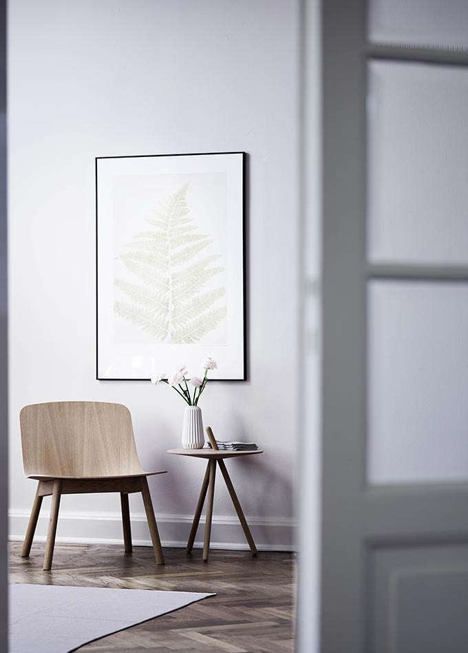 The Would Come Here side table designed by Steffen Juul in a vignette paired with a chair and an art print on the wall. Image by Nest.co.uk.