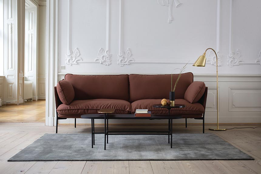 What a lovely sofa! Love this rusty color of the sofa against the white wall and its decorative moldings. The brass floor lamp and the black coffee table look so contemporary. They're paired with a gray area rug. Image by Nest.co.uk.