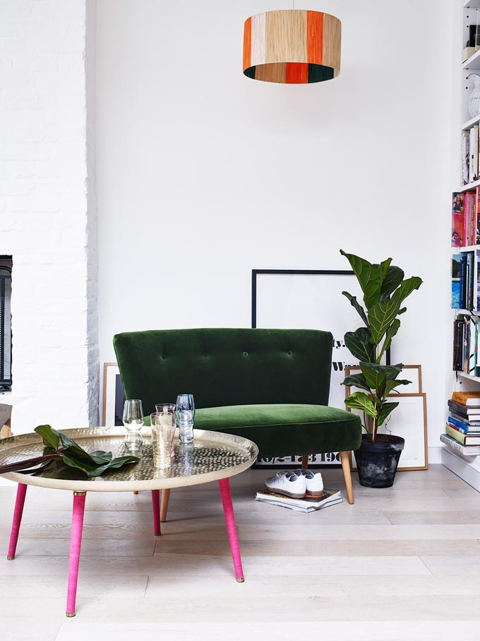 Awesome! A deep green velvet sofa looks fab in an all white interior, next to a green plant and paired with an really cool round brass metallic coffee table with pink legs. Image by Oliver Bonas.