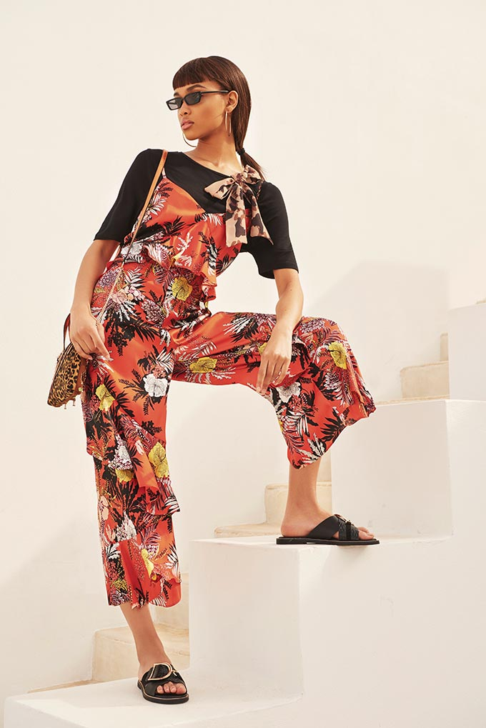 Does this qualify as a jumpsuit or overalls? This model is wearing a bright floral print jumpsuit with spaghetti strings and a black tee under it, paired with a leopard print handbag and black sliders. Cool! Image by River Island.