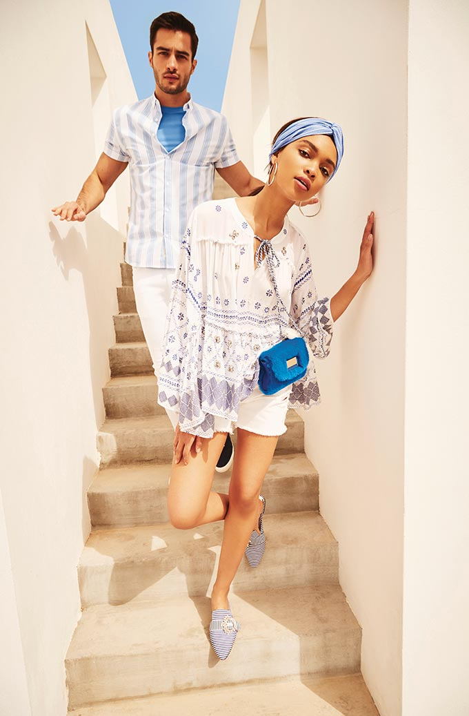Blue and white. The perfect colors to wear while on vacay in Greece. This couple has nailed it. She wears a white boho shirt, shorts and sliders. He wears a striped shirt and white pants. Image by River Island.